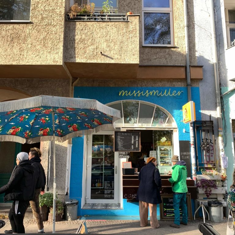 front view of the rudimarie cafe, blue walls and a big window, a big umbrella and 4 people in front