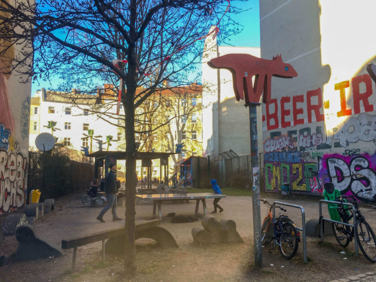 a playground for children in Neukölln with benches and tables with a big tree in front and buildings in the back.