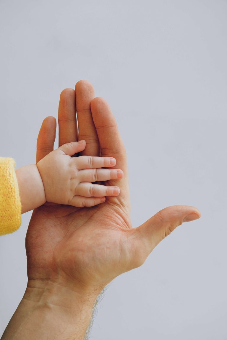 a hand of an adult holding a hand of a newborn