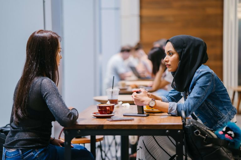 2 women having a conversation in a cafe