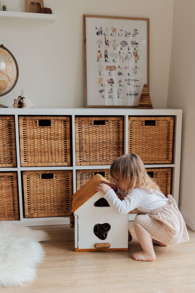 a little girl is playing with a doll house inside a room, clothes organizers are in the back