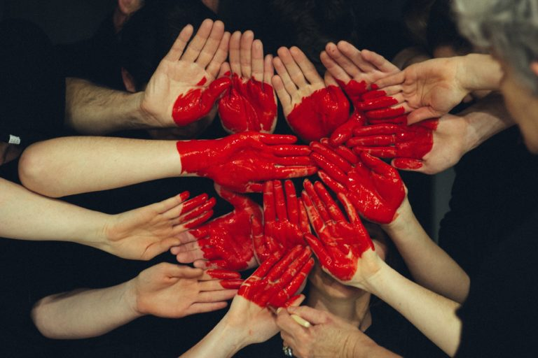 hands of many people and red heart drawn on them
