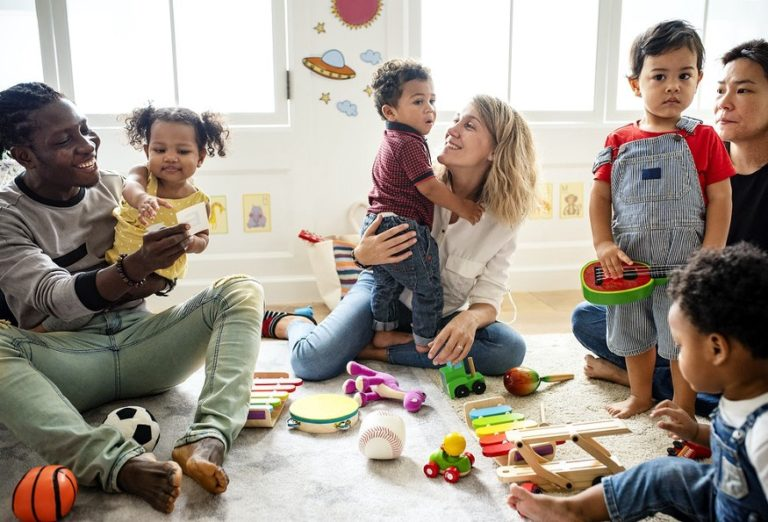 parents hug and play with their children in a kindergarten room