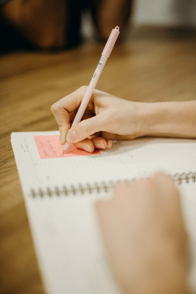a hand writing in a notebook